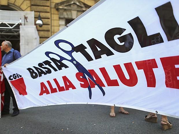 """Cartaz que diz """"Pare corte de recursos ao serviço da saúde"""" é exibido durante protesto em frente ao Ministério da Economia, em Roma (Foto: Alessandro Bianchi/Reuters)"""