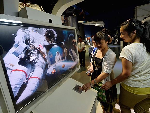 Jovens assistem a vídeo sobre espaço em museu da China (Foto: Mark Ralston/AFP)