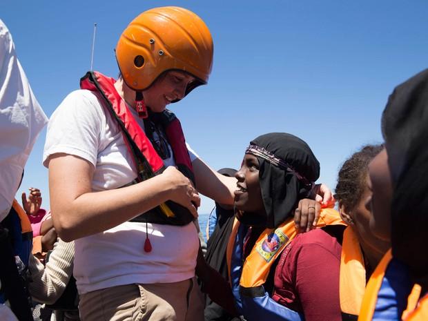 Profissional da equipe de resgate interage com migrante durante operação (Foto: Anna Surinyach/MSF)