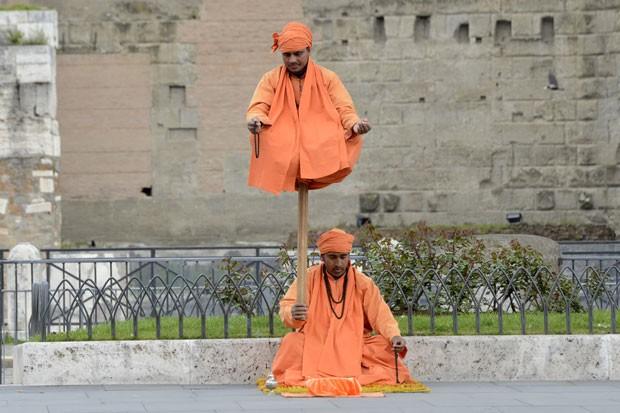 Vestidos com roupas e turbantes laranjas, artistas de rua simulam levitação nas ruas de Roma, na Itália (Foto: Andreas Solar/AFP)