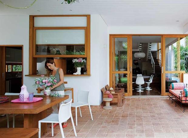 Este terraço é integrado à cozinha pela janela guilhotina e à sala de jantar (à dir.) pelos painéis deslizantes com vidro. Projeto assinado pelo arquiteto Jorge Siemsen (Foto: Edu Castello/Casa e Jardim)