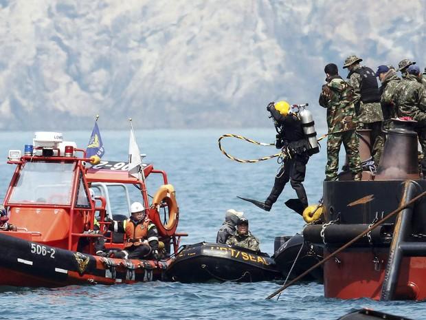 Mergulhador pula no mar na região onde balsa afundou na Coreia do Sul durante trabalhos de resgate das vítimas nesta sexta-feira (25) (Foto: AP/Yonhap)