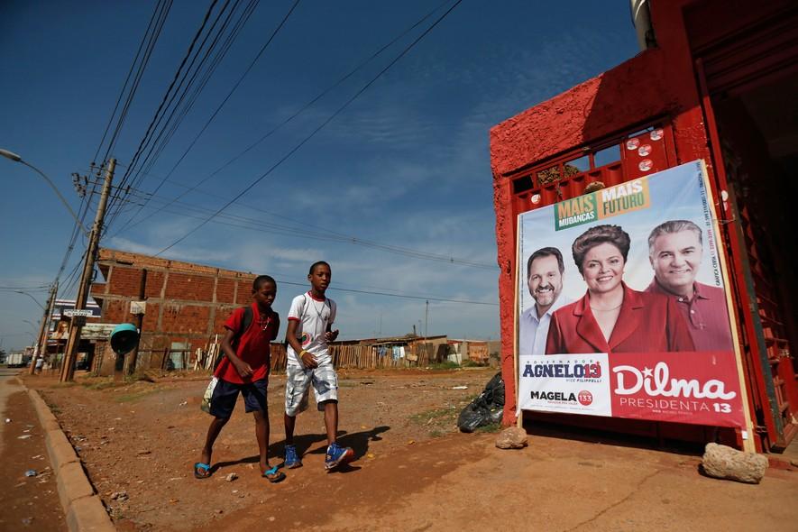 Em cidade satélite de Brasília, crianças passam por propaganda de Dilma, do governador Agnelo Queiroz e do candidato ao senado Geraldo Magela. Os dois petistas foram derrotados, e Dilma ficou em terceiro lugar no primeiro turno no Distrito Federal.