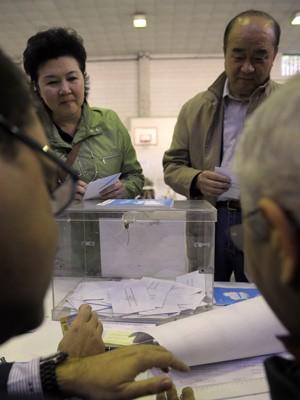 Casal vota em colégio eleitoral na Galícia, neste domingo (21) (Foto: Miguel Riopa / AFP)
