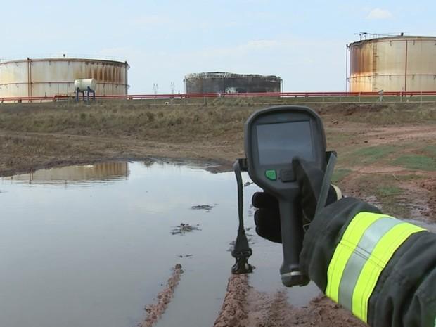 Bombeiro faz a medição da temperatura do tanque (Foto: Reprodução / TV TEM)