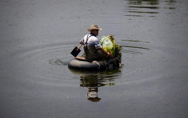 Um pescador chinês usou a criatividade e transformou uma câmara de pneu em um barquinho improvisado para pescar em um canal em Pequim, na China. (Foto: David Gray/Reuters)