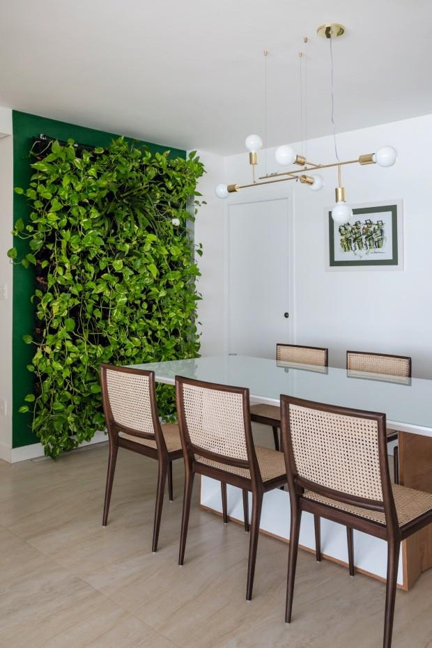 Sala de jantar. O jardim vertical recebeu uma moldura verde e fica na entrada do apartamento. Na parede, quadro do artista Carlos Páez Vilaró (Foto: Julia Ribeiro / Divulgação)