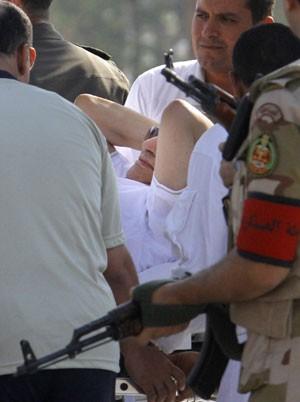 Hosni Mubarak, de 85 anos, é levado de maca por médicos e militares ao chegar de helicóptero ao hospital militar Maadi, vindo da prisão Torah (Foto: Amr Nabil/AP)