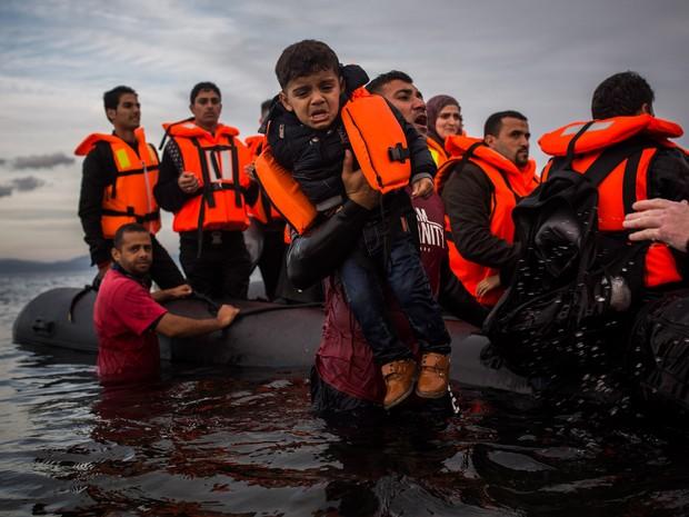 Voluntários ajudam refugiados a sair de um bote após eles cruzarem parte do mar Egeu da Turquia para a ilha grega de Lesbos. Vários países europeus declararam que só irão permitir a entrada de refugiados de zonas de guerra do Afeganistão, Iraque e Síria (Foto: Santi Palacios/AP)