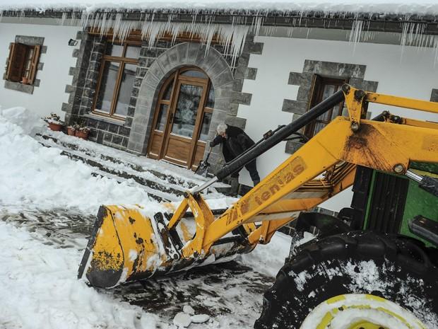 Morador retira a neve da entrada de sua casa, enquanto um trator limpa a rua na cidade de El Espinal, na Espanha, na quinta-feira (5) (Foto: AP Photo/Alvaro Barrientos)