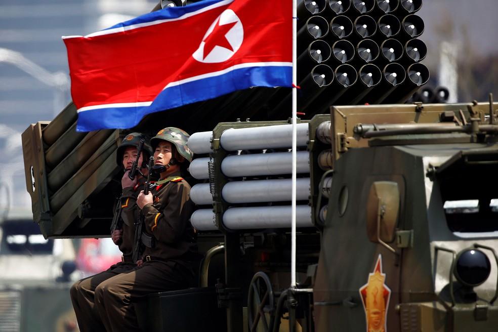 Soldados detêm armas sentados em um veículo carregando foguetes enquanto passam pelo estande com o líder norte-coreano Kim Jong Un durante desfile militar marcando o 105º aniversário de nascimento do pai fundador do país, Kim Il Sung, em Pyongyang, nesta sábado (15) (Foto: REUTERS/Damir Sagolj)