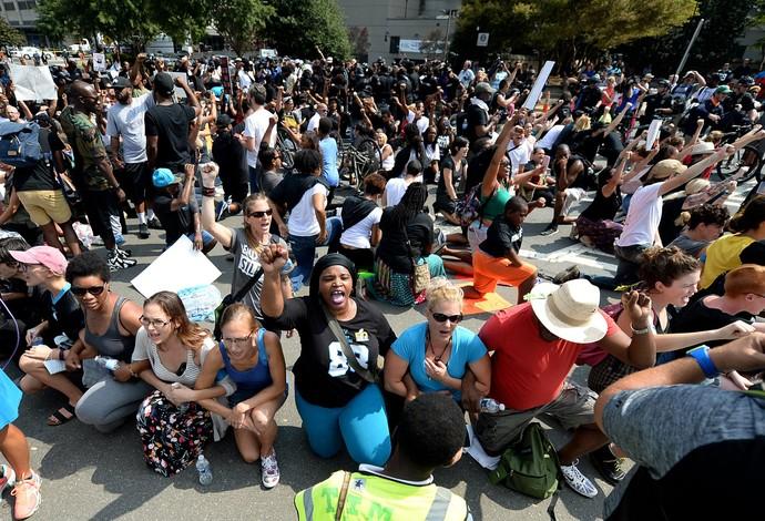 Pessoas se ajoelham durante hino dos EUA em protesto contra policias nas ruas de Charlotte (Foto: (Jeff Siner/The Charlotte Observer via AP)