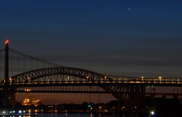 Vênus (esquerda) e Júpiter (direita) aparecem juntos em uma rara visão sobre as pontes Hell e  Robert F. Kennedy, na manhã desta segunda-feira (18) (Foto: Stan Honda/AFP)