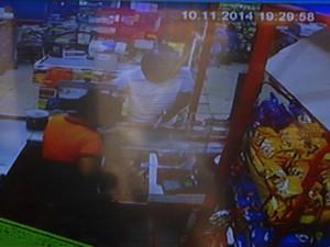 Bandido ameaçou funcionária com revólver, pegou dinheiro e fugiu em motocicleta que estava com parceiro foram do estabelecimento (Foto: Reprodução/TV Tapajós)