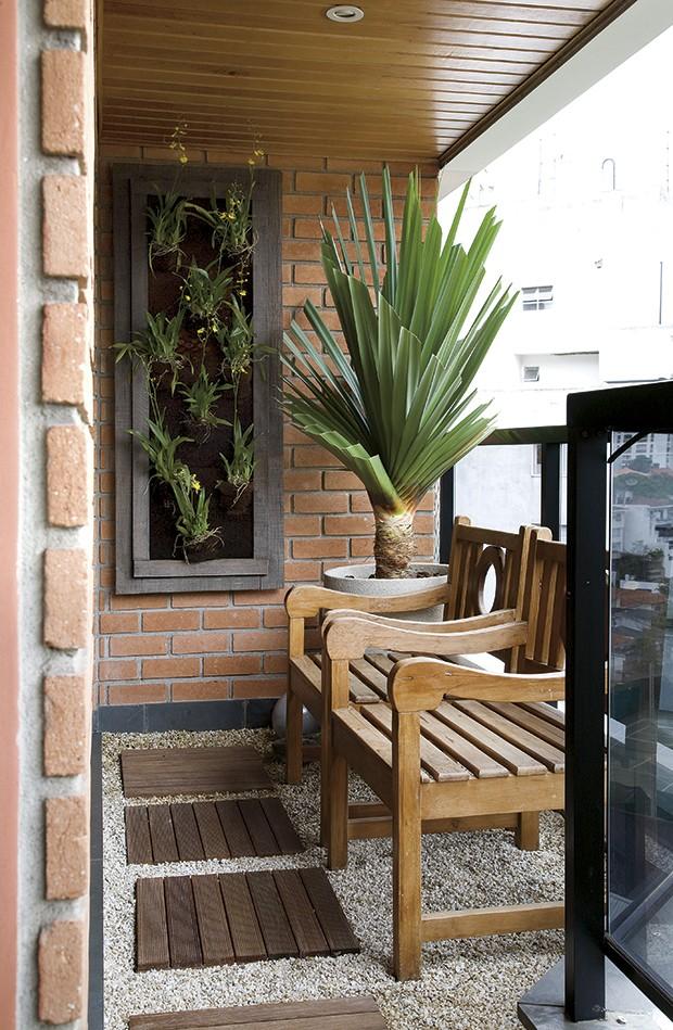 Mesmo pequena, a varanda tem espaço para as poltronas de madeira de demolição e o vaso de granilite com pândano. O painel com orquídeas-chuva-de-ouro aumenta a presença de plantas. Projeto da paisagista Paula Magaldi (Foto: Evelyn Müller/Casa e Jardim)