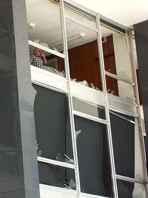 Homem fala ao telefone junto a janela com vidros quebrados no STF (Foto: Fausto Carneiro/G1)