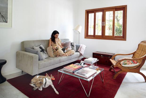 a sala tem sofá deFernando Jaeger, tapete Puntoe Filo, mesas de centro da Empório Vermeil, com design do estúdio Nada Se Leva,e livros da Livraria Cultura. Na cadeirae no sofá, almofadas de Marcela Pepe. Embaixo da janela, baú da Ethnix. Da Artemide, lumi (Foto: Victor Affaro)