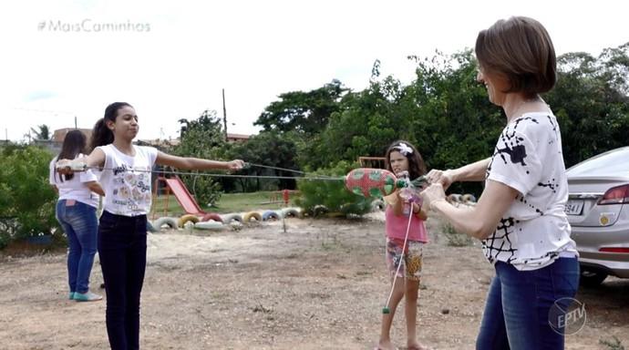 """Edlaine Garcia e as crianças brincam com os presentes do prjoeto """"Boneco de Lata"""" (Foto: reprodução EPTV)"""