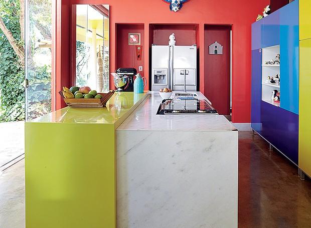 """A cozinha do arquiteto Leo Romano é um exemplo da decoração """"color block"""", tendência em que cores fortes e lisas são misturadas sem medo. As paredes vermelhas contrastam com armários azuis e bancada verde (Foto: Victor Affaro/Casa e Jardim)"""