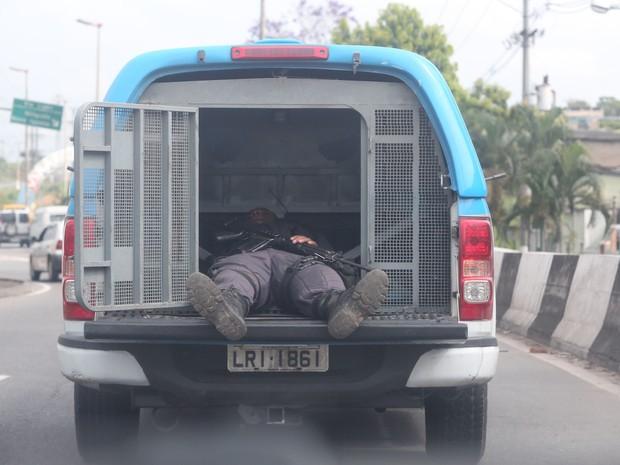 Policial dormindo no porta-mala da viatura onde coloca os preso na estrada Rio do Pau, Pavuna, proximo a entrada do Chapadão. (Foto: DANIEL CASTELO BRANCO/AGÊNCIA O DIA/ESTADÃO CONTEÚDO)