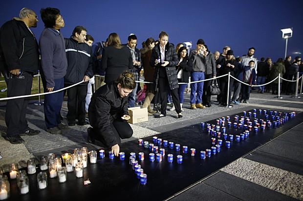 Mulher ajeita velas que formam 'Arik' Sharon perto do caixão onde é velado neste domingo (12) o corpo do ex-premiê, na esplanada do Knesset, em Jerusalém (Foto: Ronen Zvulun/Reuters)