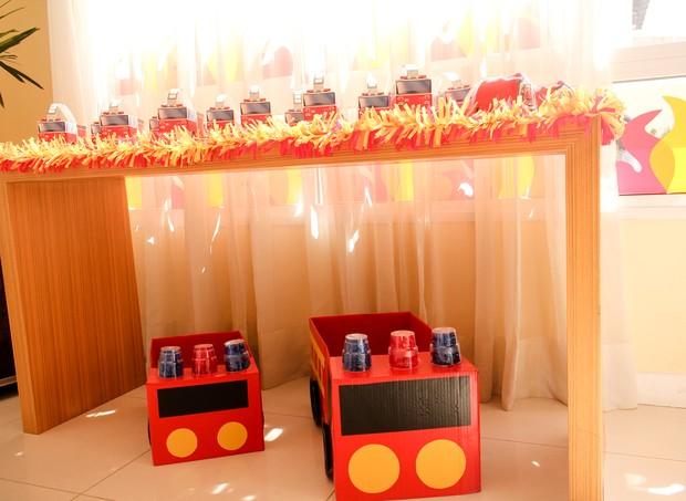 Mesa com carros de bombeiro feitos de papelão foram a lembrancinha da festa (Foto: Arquivo Pessoal)