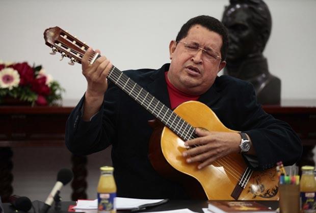 O presidente da Venezuela, Hugo Chávez, toca violão durante reunião ministerial nesta quinta-feira (20) (Foto: Reuters)