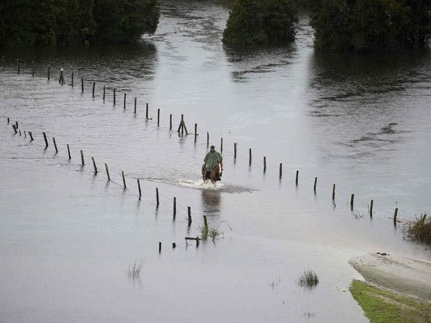 Homem anda a cavalo em estrada inundada perto de Puerto Varas, no Chile, nesta segunda-feira (2) (Foto: REUTERS/Stringer )