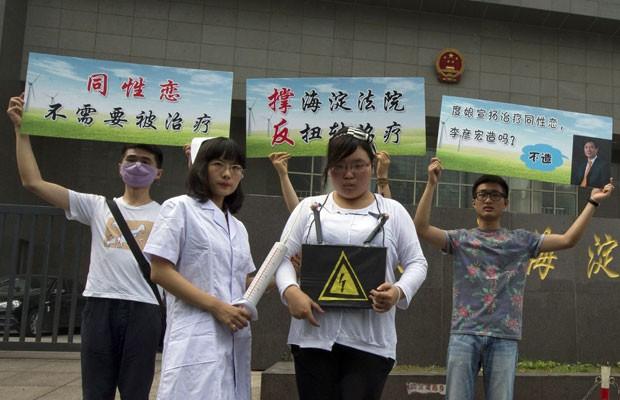 Ativistas pelos direitos dos gays protestam do lado de fora de tribunal que analisa caso envolvendo suposta terapia de conversão para homossexuais na China nesta quinta-feira (31) (Foto: Ng Han Guan/AP)