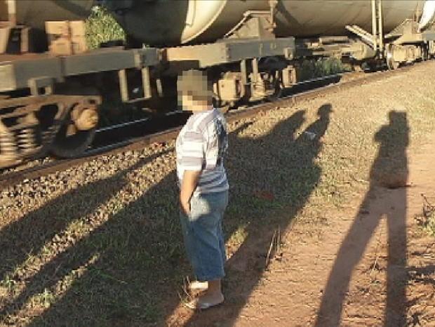Menino fica ao lado do trem, no mesmo local do atropelamento (Foto: Reprodução/TV TEM)