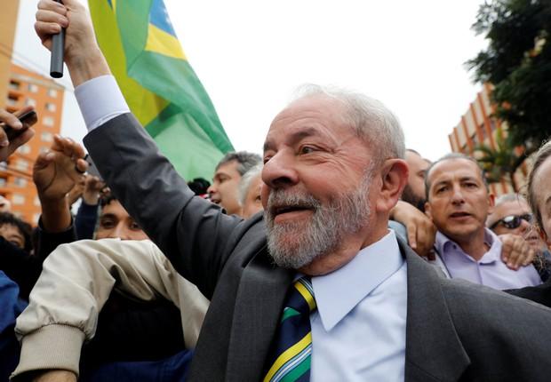 O ex-presidente Luiz Inácio Lula da Silva carrega bandeira brasileira em sua chegada ao prédio da Justiça Federal em Curitiba (Foto: Nacho Doce/Reuters)
