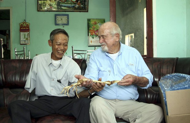 Sam Axelrad (direita) segura os ossos do braço de Nguyen Quang Hung em sua casa na cidade de An Khe, no Vietnã (Foto: AP)