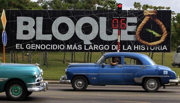 Carros passam em frente a outdoor contrário ao embargo, nesta terça-feira (13), em Havana, capital de Cuba; o texto em espanhol diz: 'Embargo: o maior genocídio da história' (Foto: Enrique de la Osa/Reuters)