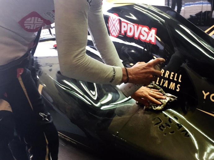 Romain Grosjean limpa carro da Lotus durante 2º treino livre para o GP da Inglaterra (Foto: Divulgação)
