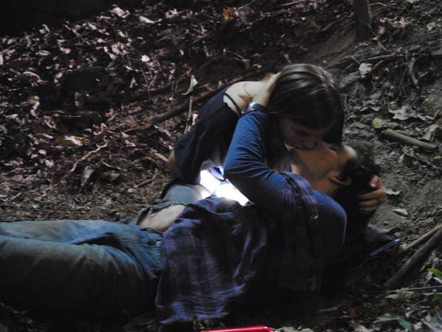 Dinho agarra Lia e tenta beijá-la no meio do mato, mesmo ferido  (Foto: Malhação / TV Globo)