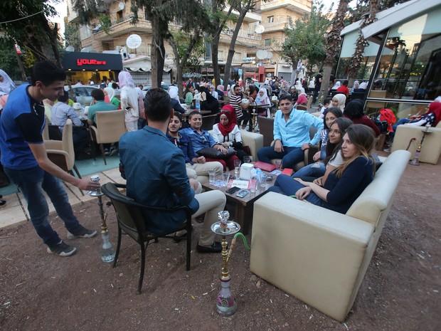 Jovens sírios se encontram em café no bairro de Mogambo, controlado pelo governo sírio em Aleppo, enquanto celebram o Eid al-Adha nesta terça-feira (13) (Foto: YOUSSEF KARWASHAN / AFP)