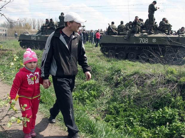 Pai e filha passam ao lado de blindados ucranianos na cidade ucraniana oriental de Kramatorsk  (Foto: Anatoliy Stepanov/AFP)