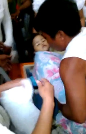 Imagem retirada de vídeo mostra criança que acordou em seu funeral sendo retirada de caixão nas Filipinas (Foto: Reprodução/YouTube/ amShare)