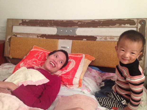 Gao Qianbo, de 2 anos, faz a mãe rir; garoto fica o dia todo ao lado da mãe acamada. (Foto: QCH/The Grosby Group)