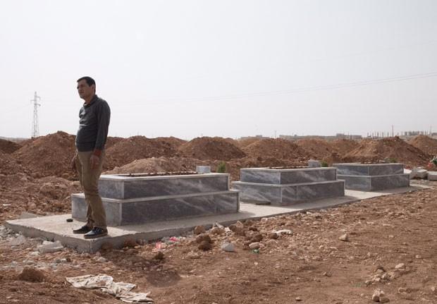 Abdullah Kurdi ao lado dos caixões estão enterrados os filhos, Alan e Galib, e a mulher, Rihan (Foto: Gabriel Chaim/G1)