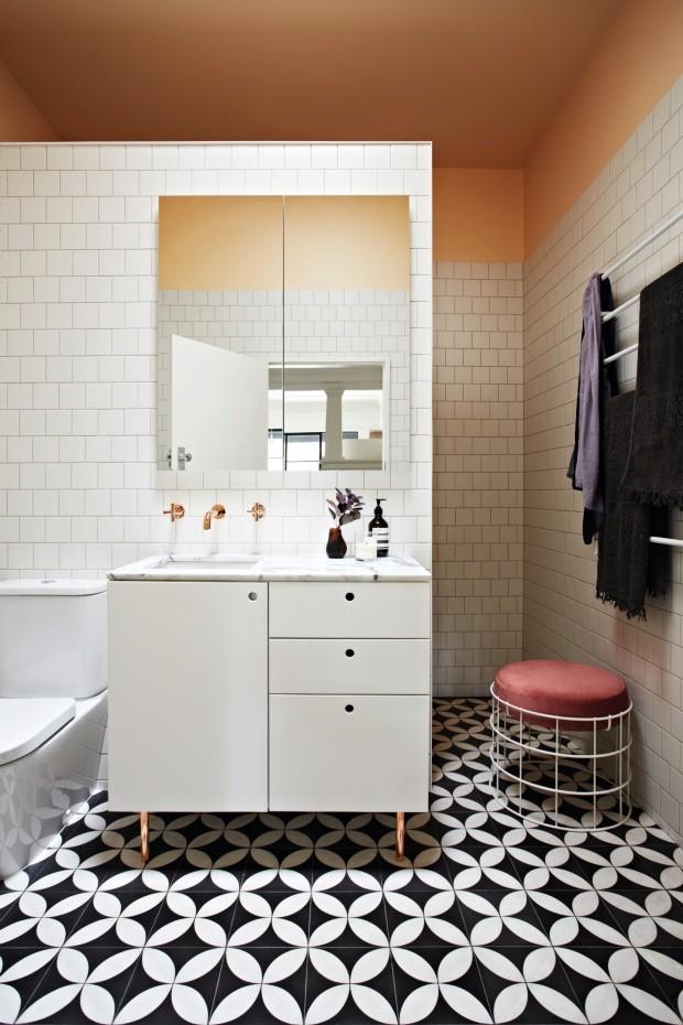 Banheiro. Tons de pêssego e cobre misturados ao ladrilho preto e branco deram um ar sofisticado ao banheiro da família (Foto: Armelle Habib / Living Inside)