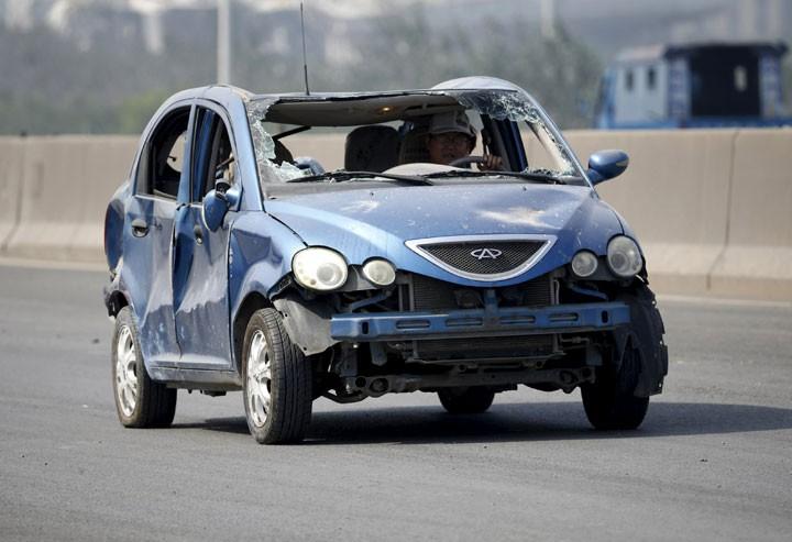 Motorista conduz carro danificado perto do local da explosão em Tianjin (Foto: Reuters)
