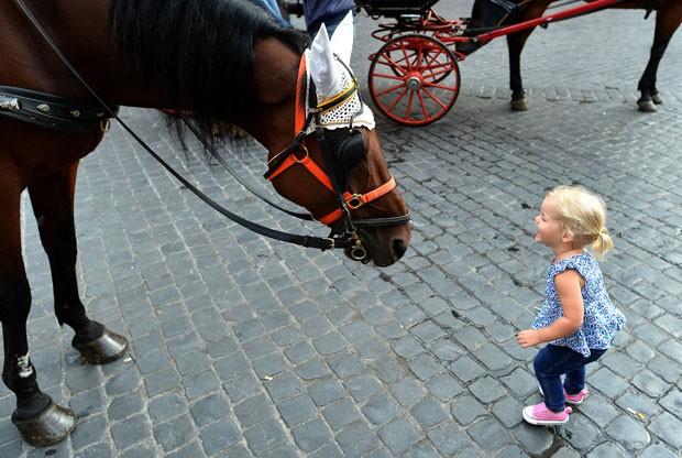 Menina se aproxima do cavalo de uma carruagem de passeio turístico no centro histórico de Roma, na Itália (Foto: Alberto Pizzoli/AFP)