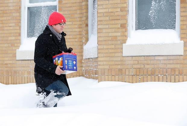 Homem é flagrado enfrentando neve para comprar cerveja neste sábado (9) em Boston (Foto: Jared Wickerham/Getty Images/AFP)