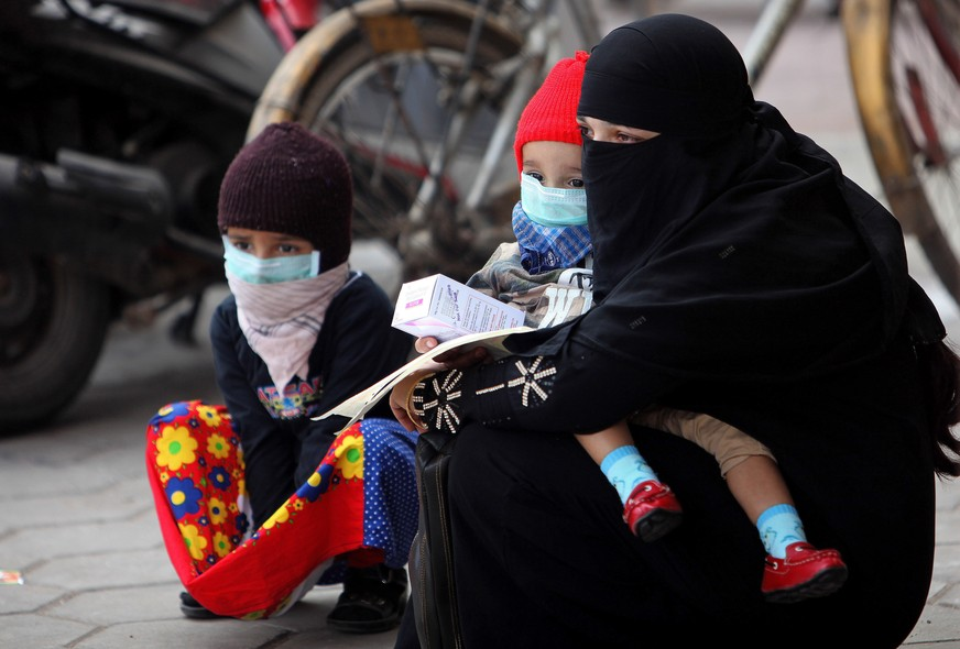 An Indian woman and her children cover their faces with masks as preventive measures against swine flu inside Gandhi Hospital premise in Hyderabad, India, Saturday, Jan. 31, 2015. Swine flu has claimed more than 20 lives in the Hyderabad region in the mon