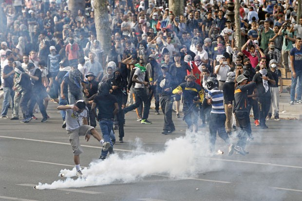 Manifestantes contrários à ofensiva israelense tentam chutar de volta as bombas de gás lacrimogêneo contra a polícia em Paris (Foto: François Mori/AP)