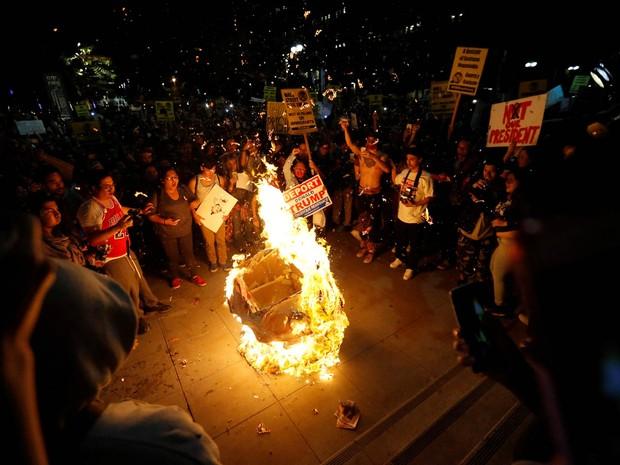 Uma piñata com o formato de Donald Trump é incendiada em uma roda de manifestantes contrários a sua eleição durante protesto no centro de Los Angeles, na Califórnia (Foto: Mario Anzuoni/AP)