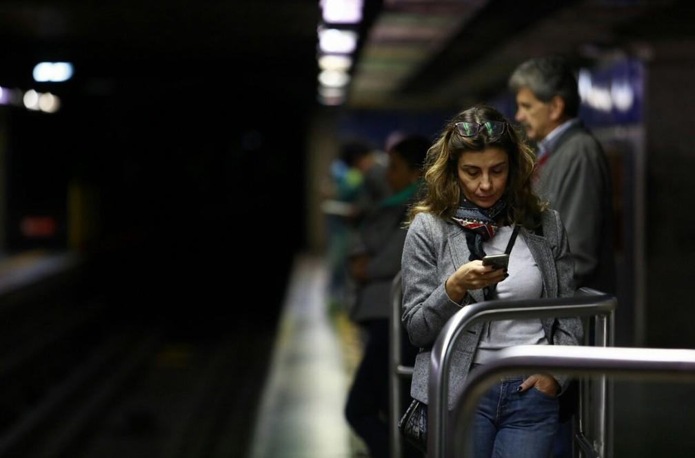 Mulher olha celular enquanto espera metrô na estação da Luz, em São Paulo. Por boa parte da manhã, a estação permaneceu fechada. (Foto: Marcelo Brandt/G1)