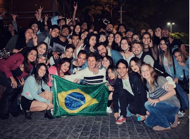 Ansel com fãs e a bandeira do Brasil (Foto: Reprodução Instagram)