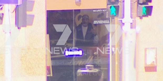Homen é visto dentro de do Lindt Cafe em Martin Place, em Sydney, durante a tomada de reféns que ocorre no local nesta segunda-feira (15) (Foto: Reprodução/Twitter/7 News Sydney)